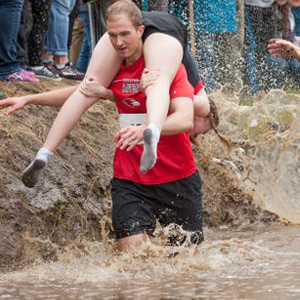 Wife Carrying Contest in America: Husbands Flow Over Many Obstacles, including Sloppy Mud and Sandstorm