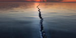Photographer captures splits 92 meter long in the ice of world's largest freshwater lake