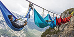 Daredevils enjoys ride in cradle which is attached to the wire between 2 mountains
